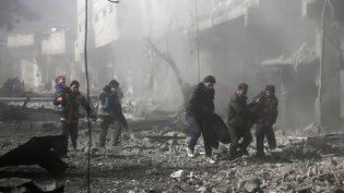 Des hommes transportent une victime après le bombardement d'un bâtiment dans la Ghouta orientale, près de Damas (Syrie), le 19 février 2018. (ABDULMONAM EASSA / AFP)