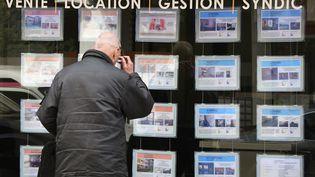 Un homme regarde des annonces dans la vitrine d'une agence immobilière. Photo d'illustration. (PASCAL PAVANI / AFP)