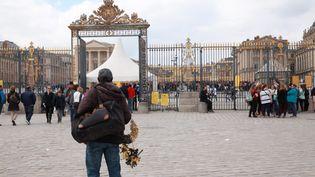 Un vendeur à la sauvette devant les grilles du château de Versailles (Yvelines), le 13 avril 2017. (MAXPPP)
