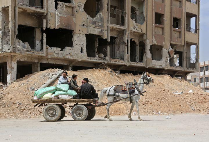 Des hommes se déplacent à bord d'une charrette dans une rue de Douma (Syrie), fief rebelle de la Ghouta orientale repris par l'armée syrienne, le 17 avril 2018. (AFP)