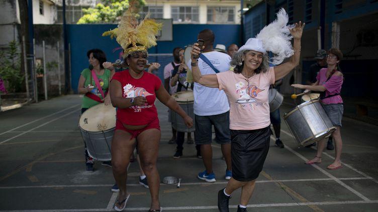 """Ariadne Mendes (à droite), psychologue et membre fondateur de Loucura Suburbana, en répétition avec les patients pour le carnaval de rue """"Loucura Suburbana"""" (folie de banlieue) à l'hôpital psychiatrique municipal Nise da Silveira, à Rio de Janeiro, Brésil, le 14 janvier 2020. (MAURO PIMENTEL / AFP)"""