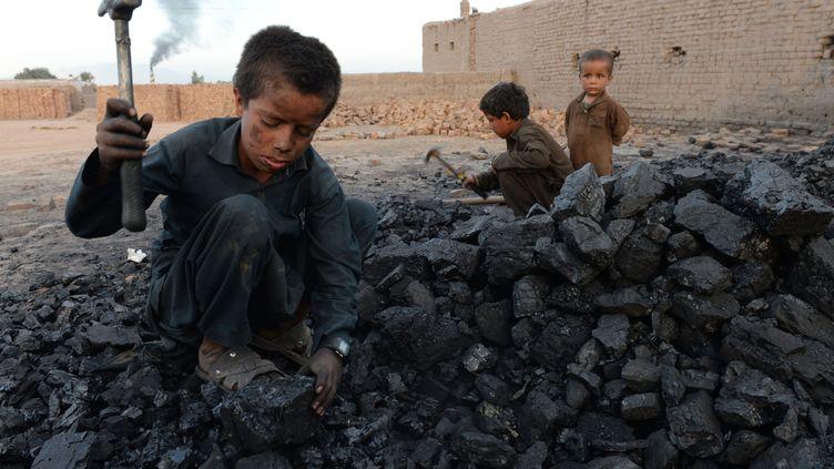 Des enfants taillent des morceaux de charbon à Jalalabad (Afghanistan), le 28 avril 2018. (NOORULLAH SHIRZADA / AFP)