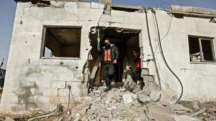 Des membres de la défense civile palestinienne inspectent une maison à Gaza, le 15 décembre 2020, après un bombardement de l'artillerie israélienne. (MAHMUD HAMS / AFP)