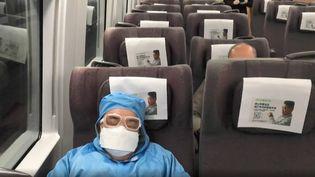 Un passager en combinaison intégrale somnole dans le train pour Wuhan, en Chine. (AFP)