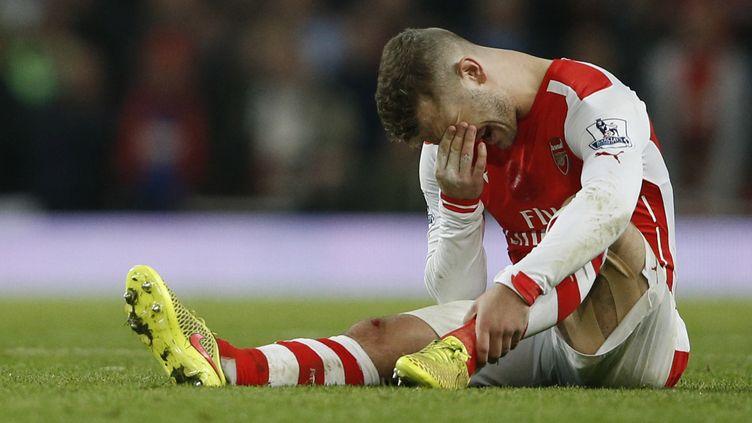 Jack Wilshere au sol, ne fera pas son retour cette semaine avec les Gunners (ADRIAN DENNIS / AFP)