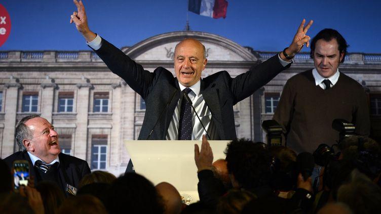 Alain Juppé(UMP) célèbre sa réélection à la mairie de Bordeaux (Gironde) au premier tour des municipales, le 23 mars 2014. (JEAN-PIERRE MULLER / AFP)