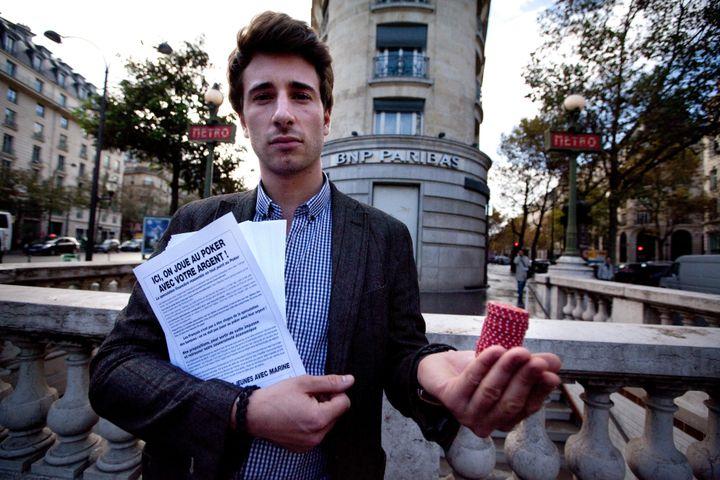Julien Rochedy distribue des tracts devant la banque BNP Paribas à Paris, en octobre 2011, lors d'une action du FNJ. (PHILIPPE HUYNH-MINH / MAXPPP)