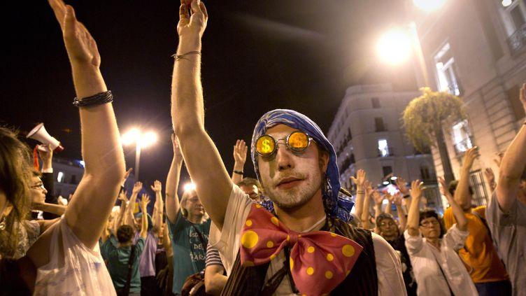 """Des """"indignados"""" espagnols respectent une minute de silence bras levés, le 12 mai 2012, sur la place de la Puerta del Sol à Madrid, pour l'anniversaire du mouvement. (JAIME REINA / AFP)"""