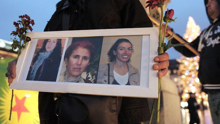 Une femme brandit le portrait des trois militantes kurdes assassinées à Paris, lors d'une manifestation à Strasbourg, le 10 janvier 2013. (FREDERICK FLORIN / AFP)