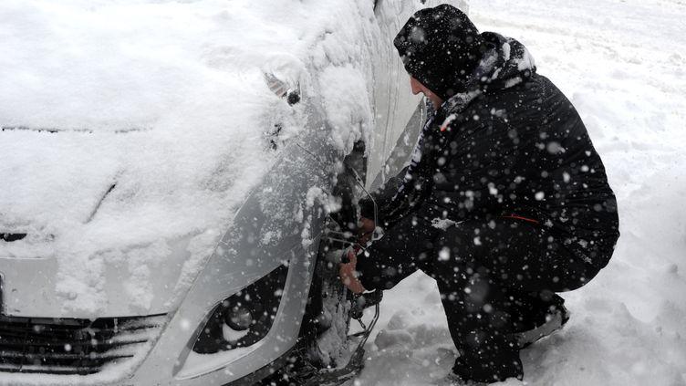 Un automobiliste équipe son véhicule de chaînes à neige sur la route des Saisies en Savoie (JEAN-PIERRE CLATOT / AFP)