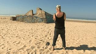 L'artiste allemand Bernd Stöcker sur la plage de Naujac-sur-Mer en Gironde où il a découvert il y a une quarantaine d'années les blockhaus érigés par les nazis pour former le Mur de l'Atlantque.  (culturebox - capture d'écran)