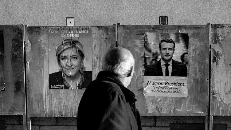 Un homme regarde les affiches électorales, devant un bureau de vote à Lyon, le 21 avril 2017. (JEFF PACHOUD / AFP)