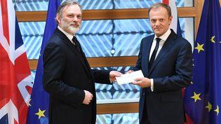 Tim Barrow (à gauche), ambassadeur du Royaume-Uni auprès de l'Union européenne, remet à Donald Tusk la lettre qui déclenchele Brexit, à Bruxelles (Belgique), le 29 mars 2017. (EMMANUEL DUNAND / POOL / AFP)