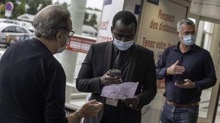 Un homme contrôle le pass sanitaire d'un client, le 9 août 2021 à l'entrée d'un centre commercial de Nantes (Loire-Atlantique). (ESTELLE RUIZ / HANS LUCAS / AFP)