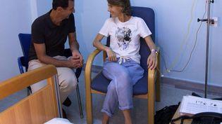 Une photo diffusée par la présidence syrienne, mercredi 8 août 2018, montre Bachar Al-Assad et sa femme, Asma, dans unhôpital de Damas (Syrie). (SYRIAN PRESIDENCY ON FACEBOOK / AFP)