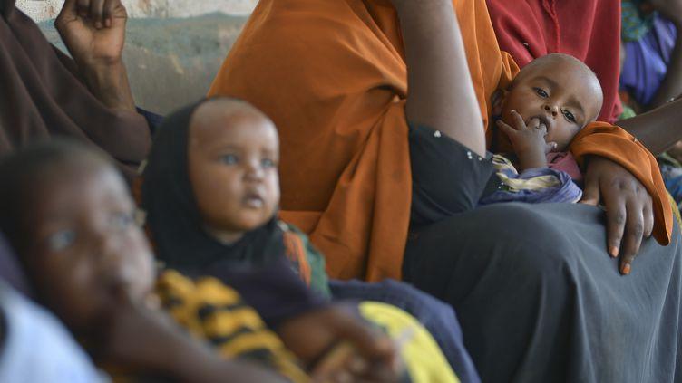 Des enfants souffrant de malnutrition attendent avec leur mère devant un centre d'aide de l'Unicef à Baidoa, en Somalie, le 15 mars 2017. (TONY KARUMBA / AFP)