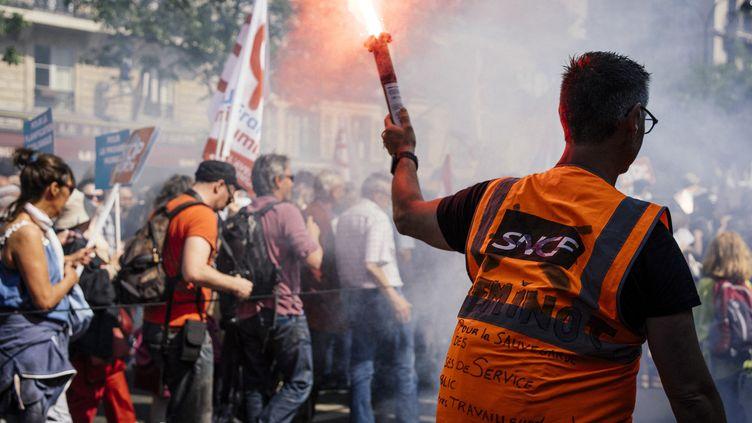 Des manifestants défilent pendant la Fête à Macron, samedi 5 mai, à Paris. (DENIS MEYER / HANS LUCAS / AFP)