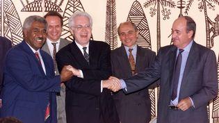 Le Premier ministre Lionel Jospin, entouré de Roch Wamytan, leader des indépendantistes néo-calédoniens, et de Jacques Lafleur, dirigeant loyaliste, lors de la signature de l'accord de Nouméa, le 5 mai 1998. (PASCAL GUYOT / AFP)