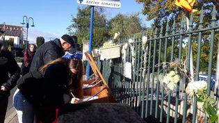 Des personnes signentle registre de condoléance àSaint-Féliu-D'avall. (JEROME JADOT / RADIO FRANCE)