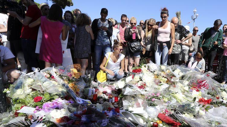 Des habitants se recueillent dans une rue de Nice, au lendemain de l'attaque au camion menée sur la promenade des Anglais, vendredi 15 juillet 2016. (VALERY HACHE / AFP)