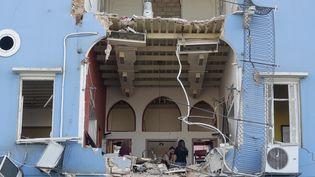 Un couple de Libanais contemple les dégâts dans leur habitation de Beyrouth, au lendemain de la double explosion qui a retenti dans le port de la capitale libanaise, mardi 4 août 2020. (JOSEPH EID / AFP)