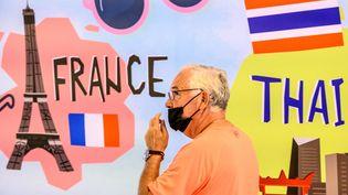 Un homme portant un masque pour se protéger du Covid-19 marche devant un panneau représentant la Tour Eiffel à Bangkok, en Thaïland, le 17 février 2020. (MLADEN ANTONOV / AFP)