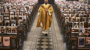 Le père Georges Nicoli, prêtre de Notre-Dame de Lourdes à Bastia, officiedevant des photos de ses fidèles paroissiens, le 9 avril 2020 (photo d'illustration). (PASCAL POCHARD-CASABIANCA / AFP)