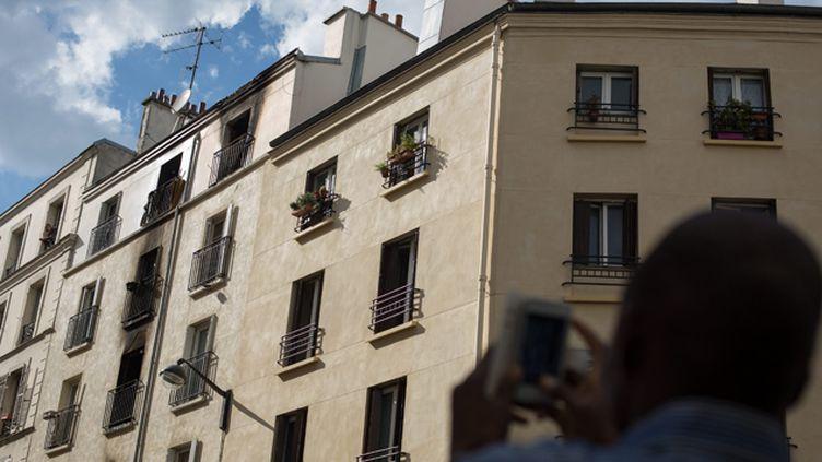 (Toute la journée de mardi, des badauds sont venus voir l'immeuble incendié provoquant la mort de huit personnes, dans le XVIIè arrondissement à Paris  © MaxPPP)