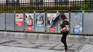 Une femme passe devant des panneaux d'affichage éléctoral en vue des élections européennes, le 19 avril 2019 à Pau (Pyrénées-Atlantiques). (LAURENT FERRIERE / AFP)