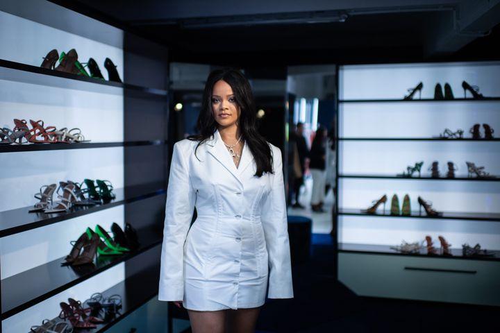 La chanteuse Rihanna pose devant des chaussures de sa collection lors d'un évènement de promotion de sa marque Fenty à Paris, le 22 mai 2019 (MARTIN BUREAU / AFP)
