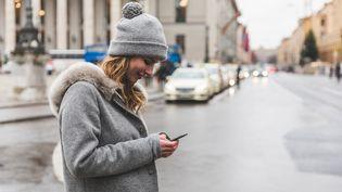 Photo d'illustration d'une femme possédant un smartphone dans la main, à Munich (Allemagne), le 12 décembre 2016. (WILLIAM PERUGINI / CULTURA CREATIVE)