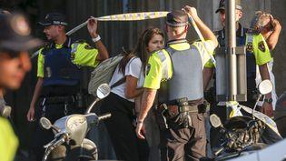 Une jeune femme quitte le périmètre de sécurité instauré autour du lieu de l'attentat de Barcelone, le 17 août 2017. (LLUIS GENE / AFP)