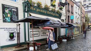 Une femme marche dansune rue à Dublin, en Irlande, le 19 octobre 2020. (PAUL FAITH / AFP)