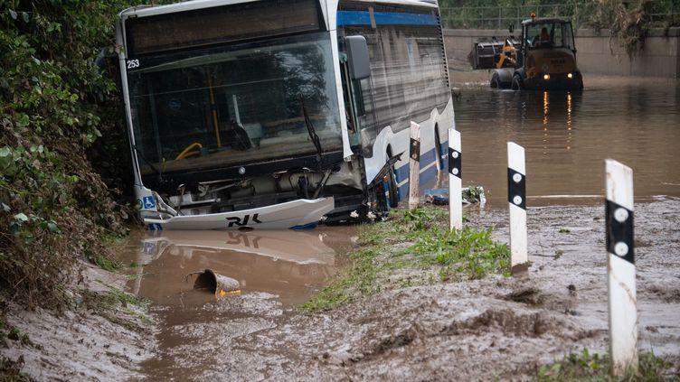Un bus gît en travers d'une route totalement submergée par l'eau et la boue à Euskirchen, en Allemagne, le 16 juillet 2021. Derrière lui, un engin de chantier tente de dégager la route. (SEBASTIEN BOZON / AFP)