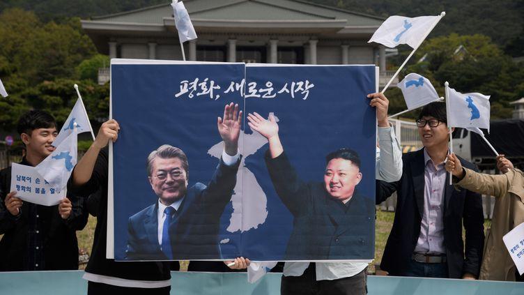 """Des militants en faveur de la paixbrandissentune photo montrantle président sud-coréen Moon Jae-in et le dirigeant nord-coréen Kim Jong-un, avec le slogan """"un nouveau départ pour la paix"""",lors d'une manifestation à Séoul, le 26 avril 2018, devant la résidence de Moon Jae-in. (ED JONES / AFP)"""
