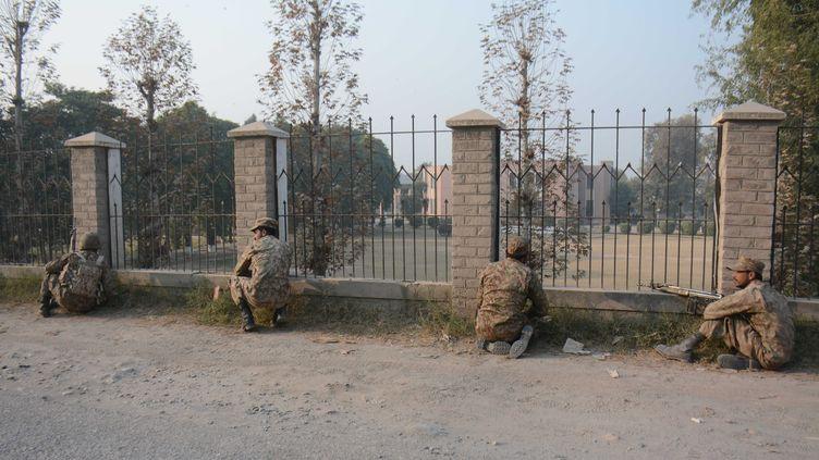 Des militaires pakistanais encerclent l'école avant de lancer l'assaut, mardi 16 décembre 2014, à Peshawar (Pakistan). (KHAN RAZIQ / ANADOLU AGENCY / AFP)