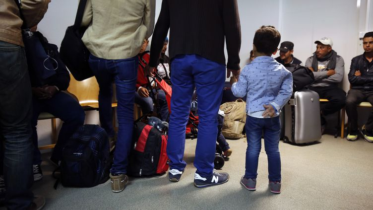 Des réfugiés venant d'Allemagne patientent dans un centre d'accueil de Champagne-sur-Seine (Seine-et-Marne), le 9 septembre 2015. (PIERRE CONSTANT / AFP)