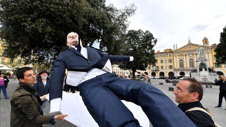 """Des militants de La France Insoumise avec un """"paillassou"""" (ici à l'effigie de Macron), à Nice le 4 mai en prélude à """"La Fête à Macron"""" organisée le lendemain à Paris. (YANN COATSALIOU / AFP)"""
