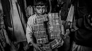 Garçon portant la monnaie afghane au marché des changes à Herat, Afghanistan 2001  (Majid Saeedi /Getty Images)