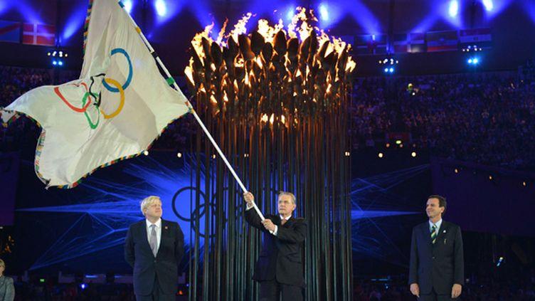 Le président du CIO Jacques Rogge, entouré du maire de Londres, Boris Johnson (à gauche), et du maire de Rio de Janeiro, Eduardo Paes. Ce passage de témoin a été effectué lors de la cérémonie de clôture des JO de Londres, le 12 août 2012. (JEFF J MITCHELL / POOL)