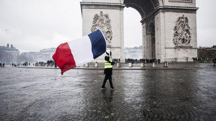 """Un homme brandit un drapeau français devant l'Arc de triomphe, lors de la manifestation des """"gilets jaunes"""", le 1er décembre 2018. (YANN CASTANIER / HANS LUCAS / AFP)"""