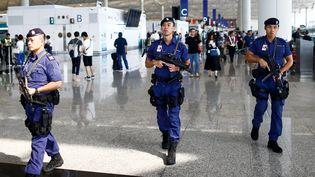 Des policiers dansle terminal de l'aéroport de Hong Kong, le 14 août 2019. (THOMAS PETER / REUTERS)