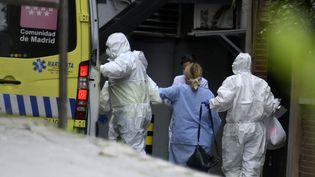 Des professionnels de santé escortent un patient à son arrivée au Gran Hotel Colon de Madrid (Espagne), un hôtel transformé en structure médicale pour traiter les cas les moins graves dans le cadre de l'épidémie provoquée par le nouveau coronavirus, le 19 mars 2020. (GABRIEL BOUYS / AFP)