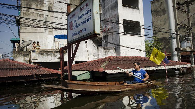 Un habitant deRangsit, près de Bangkok, se déplace en barque dans les rues inondées de la ville, le 25 octobre 2011. (NICOLAS ASFOURI / AFP)