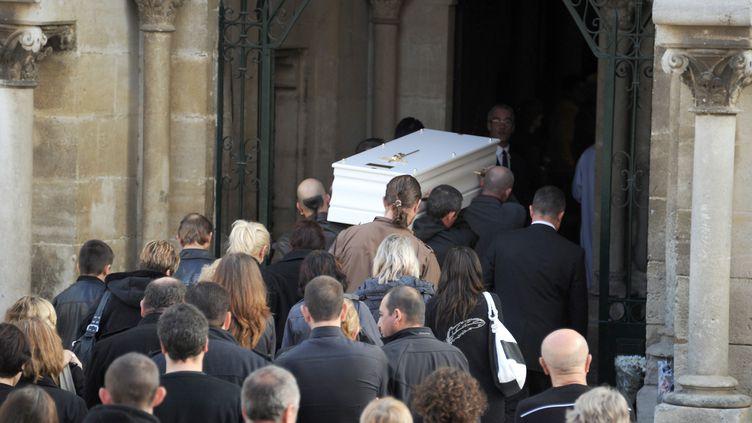Des proches transportent le cercueil de la petite Océane, 8 ans, dans l'église de Bellegarde (Gard) pour ses obsèques, le 10 novembre 2011. (PASCAL GUYOT / AFP)