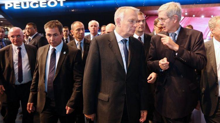 Le Premier ministre, Jean-Marc Ayrault (au c.), et le président du directoire de PSA, Philippe Varin (à dr.), sur le stand du constructeur installé au Mondial de l'automobile à Paris, le 8 octobre 2012. (THOMAS SAMSON / AFP)