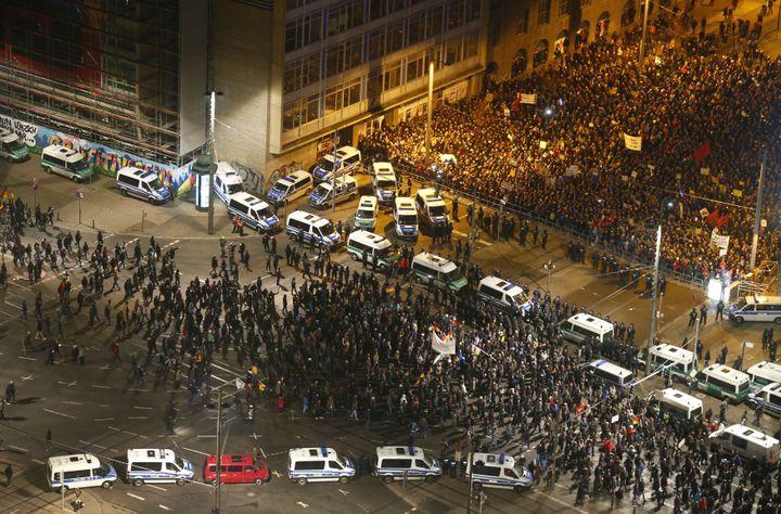 Des partisans du groupe anti-islam Legida (en bas) séparés de leurs opposants (en haut) par les forces de l'ordre, mercredi 21 janvier, à Leipzig (Allemagne). (HANNIBAL HANSCHKE / REUTERS)