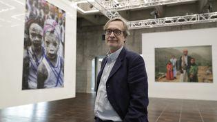 Le fondateur et président du festival Visa pour l'image de Perpignan, Jean-François Leroy est aussi le directeur artistique de L'Arche du photojournalisme à Paris. Il pose en 2017 devant le travail de l'Américaine Stéphanie Sinclair. (THOMAS SAMSON / AFP)