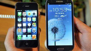 Un employé montre uniPhone 4S d'Apple (G) et un Samsung Galaxy S3 (D), dans une boutique de téléphones portables de Séoul (Corée du Sud), le 27 août 2012. (JUNG YEON-JE / AFP)