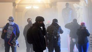 Des supporters de Donald Trump au milieu de gaz lacrymogènes, le 6 janvier 2021 dans l'enceinte du Capitole, à Washington (Etats-Unis). (SAUL LOEB / AFP)